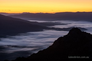 Morning mist and pre-dawn yellow sky. South West Tasmania.