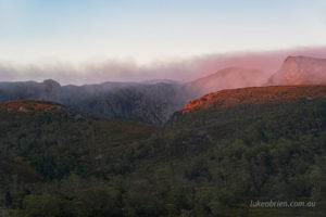 The morning light hits the mist shrouded cliffs of Crater Peak
